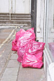 Litter bags. Litter in pink bags for collection, on a city street stock images