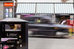 Litter bin in foreground with black cab passing by behind. Litter bin on kerb with black cab taxi passing by with blurred motion in background stock photo