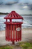 Litter bin. Red litterbin by the sea Royalty Free Stock Photo