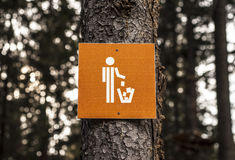 Litter bin sign in forest. The symbol of the litter bin on a tree, in a forest Stock Photos