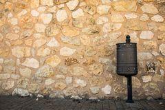 A litter bin on the street. A litter bin in the street and a stone wall in the background stock photography