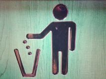 A litter bin symbol. An iconic image of a stick man depositing rubbish in a bin to instruct people to do likewise Royalty Free Stock Photography