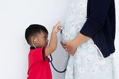 The litter boy is wearing the stethoscope. The litter boy is wearing the stethoscope and putting on belly pregnant mother Royalty Free Stock Photo