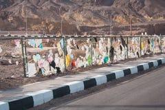 Litter in desert environment, Nuweiba. Letter blown against a fence on the side of a desert road near Nuweiba, Egypt Stock Images