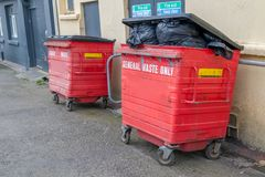 Two Litter Dumpsters on guard. Two litter dumpsters guard the fire doors at the rear of a store premises stock image