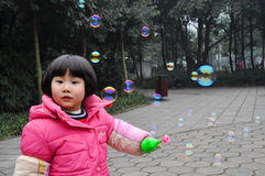A litter girl blowing bubbles Royalty Free Stock Image
