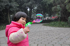A litter girl blowing bubbles stock photo