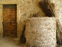 Litter roll. A bunch of straw and a big litter roll in front of an old Italian farm house Royalty Free Stock Images