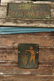 Litter sign. A pair of metal signs on a wooden bin showing a figure putting litter in a bin and the words 'DOG WASTE Royalty Free Stock Photography