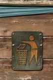 Litter sign. A metal litter sign screwed to a wooden bin showing a figure putting litter in a bin Stock Photography