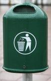 Litter in trash. A green trash bin in a city. The Bin is fastened to a lightpole Stock Photo