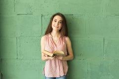 Litteratur utbildning, folkbegrepp - kvinnlig student, i att läsa boken över den gröna väggen royaltyfri foto