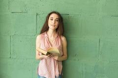 Litteratur utbildning, folkbegrepp - kvinnlig student, i att läsa boken över den gröna väggen arkivfoton
