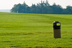 Litterbin or trash can in an open green parkland.  royalty free stock image
