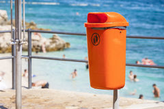 Littering the beach and the sea. Orange trash bin near the sea beach. Littering the beach and the sea Stock Images