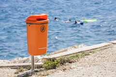 Littering the beach and the sea. Orange trash bin near the sea beach. Littering the beach and the sea Royalty Free Stock Photos