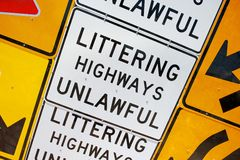 Littering Highways Unlawful Signs. A wall completely covered in old and worn road or street warning signs. This one reads Littering Highways Unlawful Stock Images