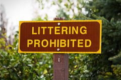 A Littering Prohibited sign with trees in the background.  Stock Photography