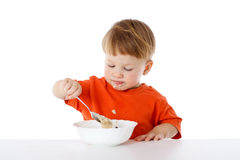 Little boy eating the oatmeal Stock Photo