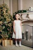 Littile-Mädchen im Kleid nahe Weihnachtsbaum mit Geschenken Stockbild