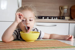 Littke girl is thinking while eating and doesn't want to eat Stock Photography