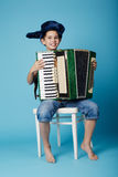 Little accordion player on blue background Stock Photos