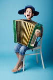 Little accordion player on blue background Royalty Free Stock Images