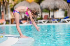 Little active adorable girl in outdoor swimming pool ready to swim. Little girl enjoy vacation in the swimming pool royalty free stock photos