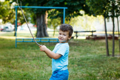 Little active boy with branch at park Royalty Free Stock Photo