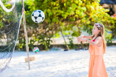 Little active girl playing voleyball on beach with ball. Sporty flid enjoying beach game outdoors Royalty Free Stock Images