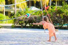 Little active girl playing voleyball on beach with ball. Sporty flid enjoying beach game outdoors Stock Photography
