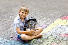Little active kid boy drawing knight castle and fortress with colorful chalks on asphalt. Happy child with big helmet royalty free stock image