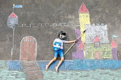 Little active kid boy drawing knight castle and fortress with colorful chalks on asphalt. Happy child in helmet and with royalty free stock photography