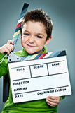 Little Actor with a Slate in His Head. Over a Grey Background Stock Photos