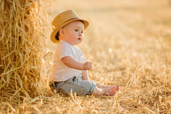Little adorable baby boy with big brown eyes in a hat sits in a Royalty Free Stock Images