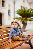 Little adorable baby boy in a straw hat and brown pants sitting Royalty Free Stock Images