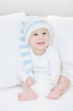 Little, adorable baby in a large white-blue hut, portrait of laughing child on white sofa Stock Images