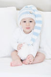 Little, adorable baby in a large white-blue hut, portrait of laughing child on white sofa Stock Photo