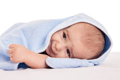 Little adorable baby lying on bed under blue towel Stock Photos