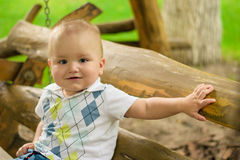 Little adorable baby sit on a bench Stock Images