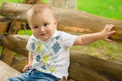 Little adorable baby sit on a bench Stock Photos