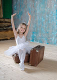Little adorable ballerina in white tutu with old vintage suitcas Stock Image
