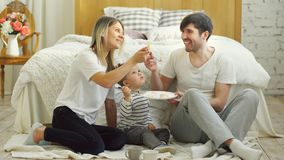 Little adorable boy celebrating his birthday with father and mother eat cake in bedroom Royalty Free Stock Photos