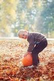 Little adorable boy is hugging a huge pumpkin in autumn garden. Royalty Free Stock Photo