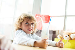 Little adorable boy sitting at table with milkshake in cafe. Portrait of little adorable boy sitting at table with milkshake in cafe Stock Image