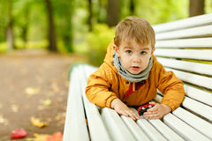 Little adorable boy in yellow jacket lying on a bench in the par Stock Photos