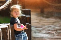 Little girl playing and having fun enjoying the spray of the fountain stock photos