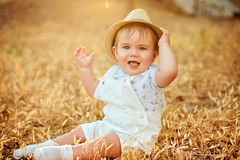 Little adorable  chubby baby boy in a straw hat and a white suit Stock Image