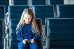 Little adorable girl in airport waiting for boarding playing with laptop. Adorable little girl in airport with her luggage Stock Photos