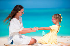 Little adorable girl applying sun cream to her mother nose Royalty Free Stock Image